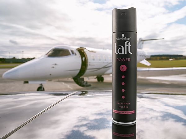 Taft hairspray in the foreground with a private jet in the background