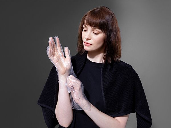 Brunette woman with black towel around her shoulders putting on some plastic gloves