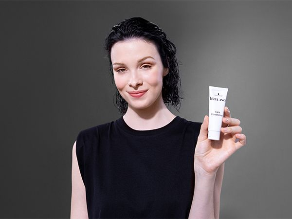 Woman with wet hair holding care conditioner in her hand