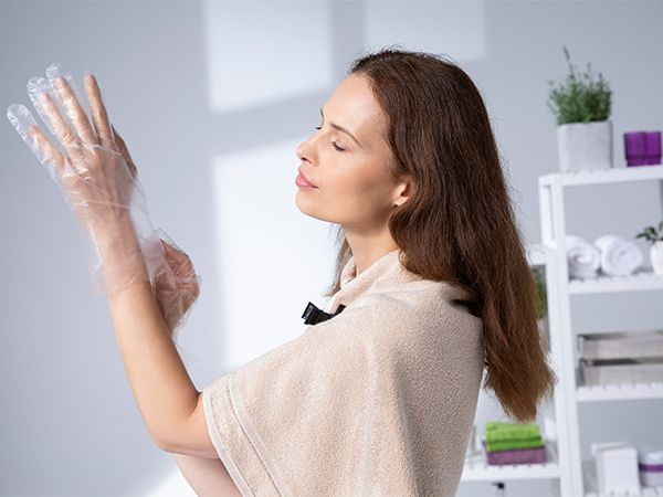 Brunette woman with beige towel around her shoulders putting on some plastic gloves