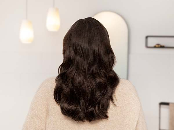 Back view of woman with dark brown, wavy hair, and peach-colored sweater