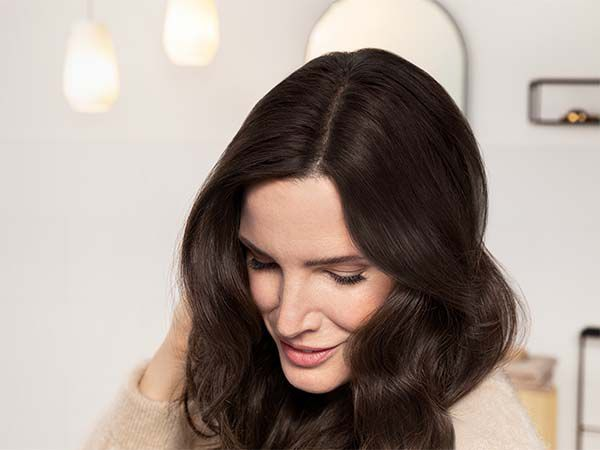Woman with dark brown hair leaning forward to show off newly-covered roots