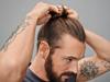 Mann mit braunen Haaren bindet sich einen Man Bun