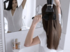 Braunhaarige Frau sieht sich im Spiegel an, während sie ihre langen Haare mit einer Bürste und einem Föhn stylt