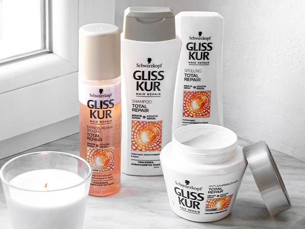 Vier Pflegeprodukte der Marke Gliss Kur stehen neben einer Duftkerze auf dem Fenstersims