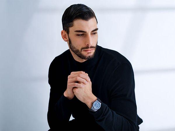 Dunkelhaariger Mann mit Bart trägt den Bro Flow-Style im Business-Look