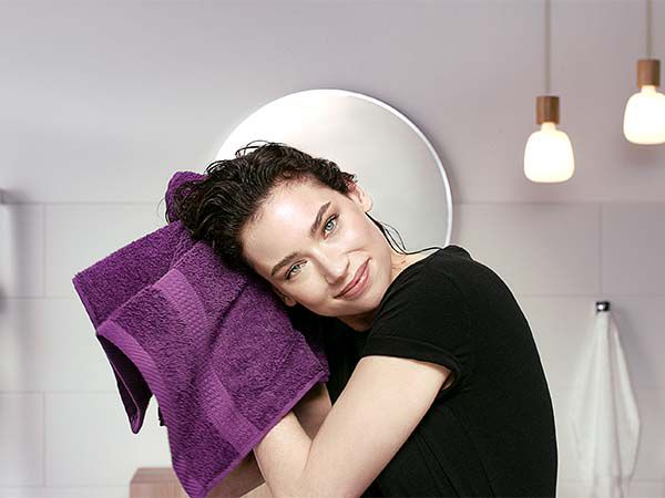 Brunette rubbing her hair dry with purple towel