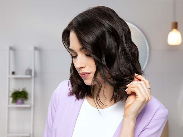 Brunette woman wearing lilac jacket touches her shiny hair