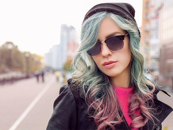 Porträt einer jungen Frau mit pastellfarbenen, lockigen Haaren, Sonnenbrille und Mütze