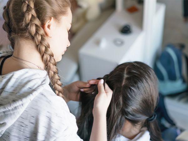 Ein blondes Mädchen mit geflochtenen Zöpfen frisiert einem brünetten Mädchen die Haare