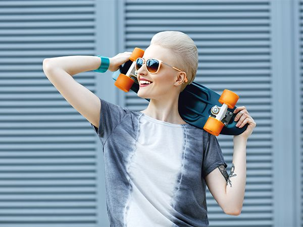 Donna bionda con acconciatura a banana e occhiali scuri, che tiene dietro le spalle uno skateboard e sorride
