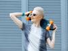 Blonde Frau mit Kurzhaarfrisur im Sleek-Look trägt Sonnenbrille, T-Shirt und auf dem Arm ein Skateboard
