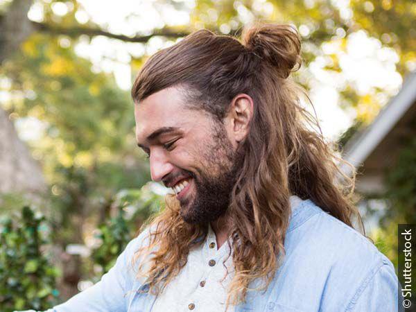 Uomo con capelli lunghi mossi raccolti in un half-up