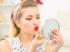 Woman dressed like pin-up girl applies lipstick while looking in a small mirror