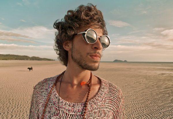 Uomo con capelli biondi corti che cammina in spiaggia