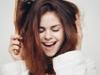 Lächelnde brünette Frau kämmt sich die Haare