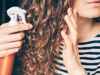 Nahaufnahme einer Frau, die mit einer Sprühflasche ihr lockiges Haar besprüht