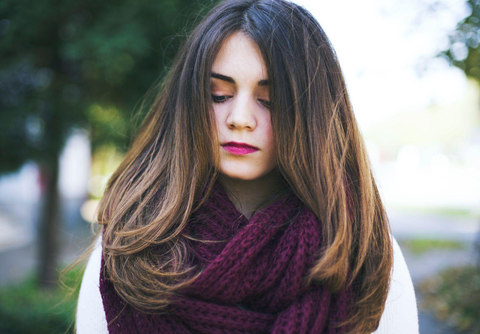 Jeune femme avec un magnifique balayage miel sur cheveux bruns et une écharpe violette