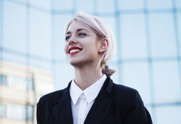 Femme aux cheveux rose blanc et au rouge à lèvres rouge se tenant devant un bâtiment en verre.