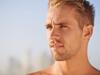 Blonder Mann mit Dreitagebart und kurz geschnittener Surferfrisur