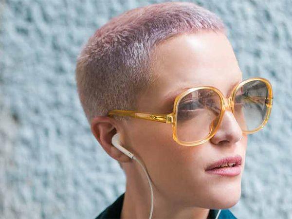 Frau mit kurzem Pixie-Haarschnitt in Pastelllila und mit Sonnenbrille