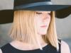 Blonde Frau mit glattem Long Bob trägt einen schwarzen Hut