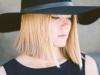 Blonde Frau mit glatter Bob-Frisur und Hut