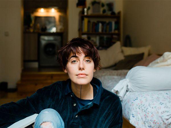 Braunhaarige Frau mit kurzer Übergangsfrisur sitzt neben ihrem Bett