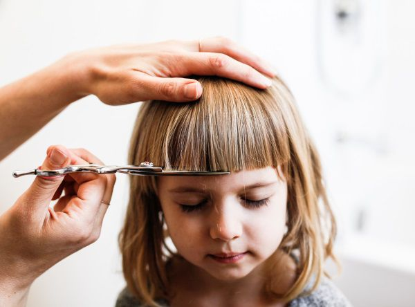 Bambina con caschetto lungo a cui stanno tagliando la frangia