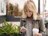 Blonde Frau mit modernem Zick-Zack-Scheitel hält Kaffeebecher und Smartphone in ihren Händen