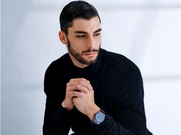 Homme avec une barbe et des cheveux bruns associant une coupe Business à un look sérieux.