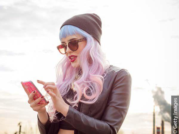 Frau mit langem Unicorn Hair, Sonnenbrille und Mütze tippt auf Ihr Smartphone