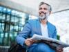 Graue Haare: Mann mit grauem Bart sitzt im Businessoutfit mit einer Zeitung auf einer Bank