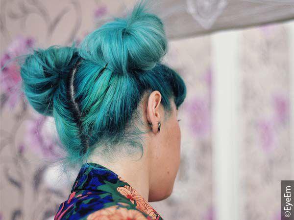 Rückansicht einer Frau mit buntem Unicorn Hair zu Space Buns gestylt