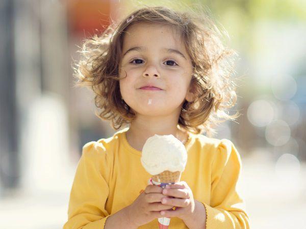 Petit fille aux cheveux châtains courts retenus par une pince en train de manger une glace.
