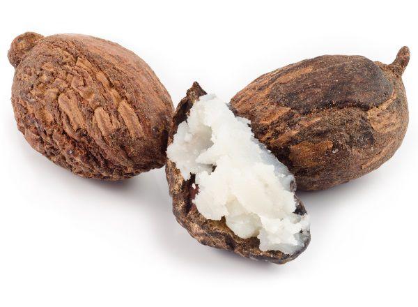 Trois noix de karité dont une est remplie de beurre de karité.