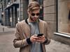 Mann mit Haaren im Undone-Look und Sonnenbrille geht mit Handy in der Hand eine Straße entlang