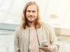 Blonder Mann mit langen Haaren und Dreitagebart lächelt in die Kamera