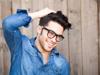 Mann mit Locken und Brille lacht