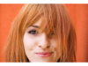 Woman with dyed red hair against an orange background
