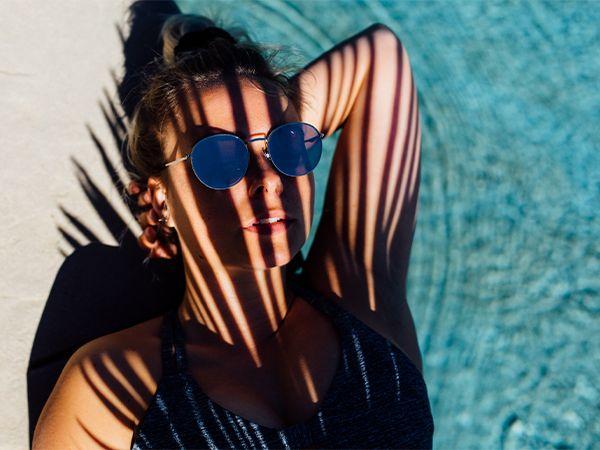 Blonde Frau mit Dutt liegt mit Sonnenbrille am Poolrand