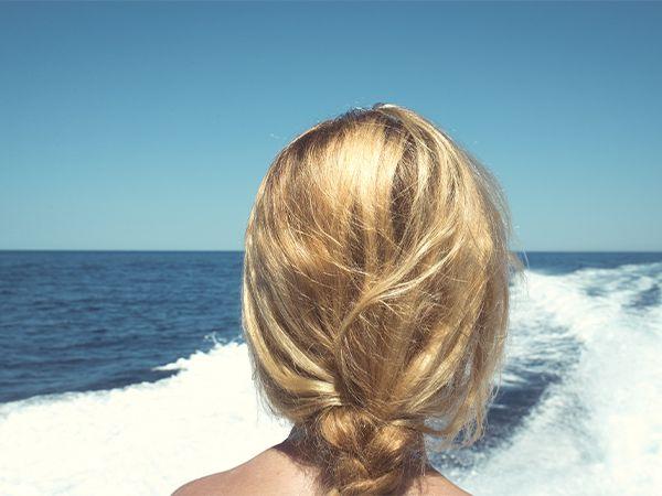 Rückansicht einer blonden Frau mit geflochtener Strandfrisur