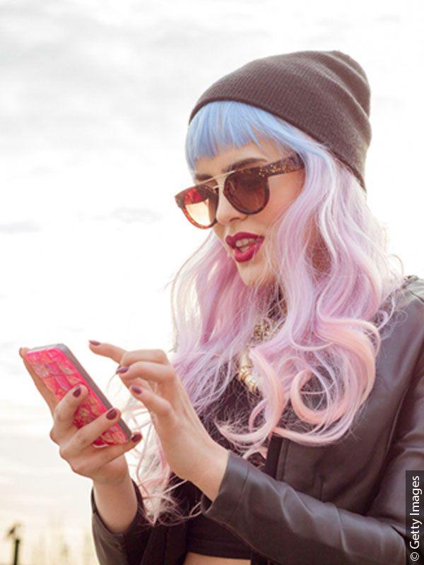 Kobieta korzystająca ze smartfona z włosami w odcieniu różu