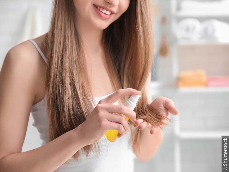 Žena sa dugom plavom kosom koja nanosi proizvod za negu krajeva