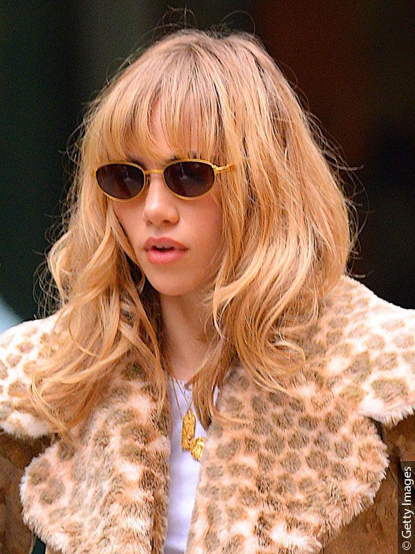 Junge Frau mit Sonnenbrille und honigblonder, mittellanger Frisur im Boho-Stil der 70er