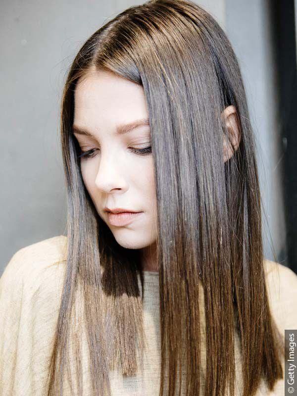 Mlada smeđokosa žena sa glatkom, lepljivom kosom i masnim korenom