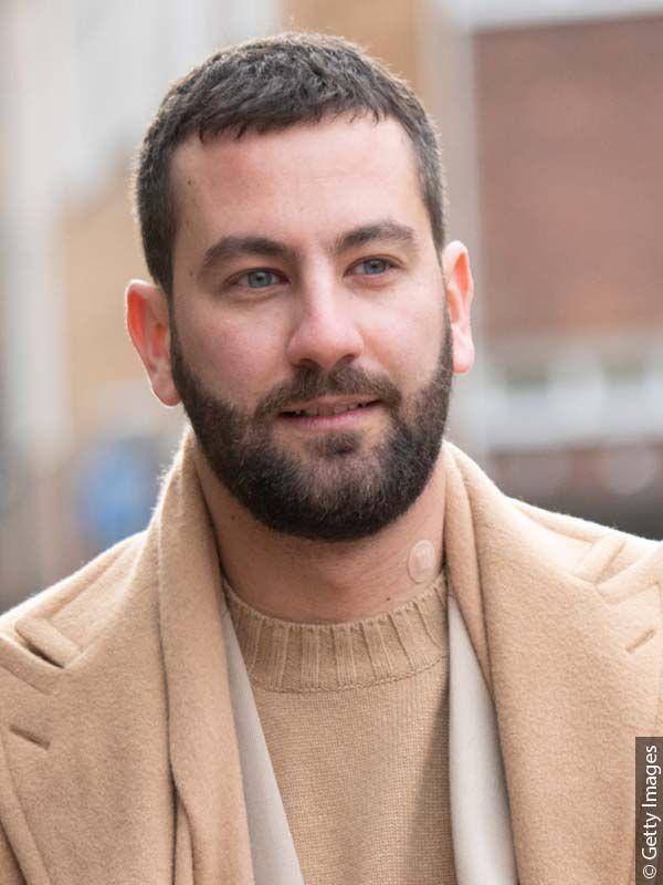 Tamnokosi muškarac u odjeći bež tonova s punom bradom i kratkom frizurom koja odvlači pozornost od njegovih zalizaka