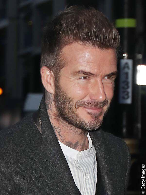 Nogometaš David Beckham u sportskom kaputu, s dužom kosom na vrhu glave i kratkom sa strane, frizura koja lijepo prikriva njegove zaliske