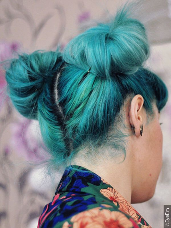 Back view of a woman with bright unicorn hair styled in space buns
