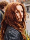 Woman with natural red hair, wearing leather jacket